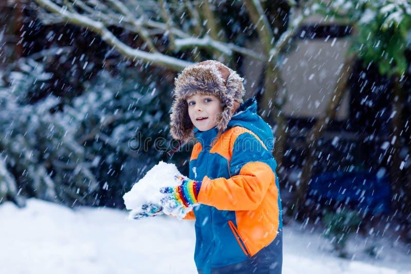 Lycklig ungepojke som har gyckel med insnöad vinter royaltyfri foto