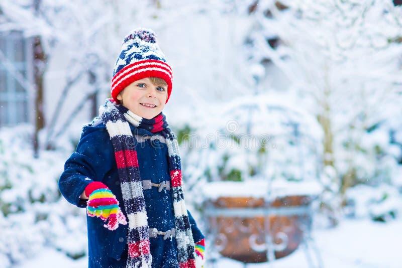 Lycklig ungepojke som har gyckel med insnöad vinter fotografering för bildbyråer
