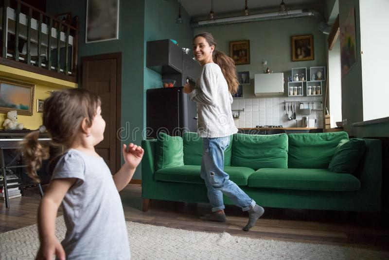 Lycklig upphetsad ensamstående mamma som spelar med dottern royaltyfri fotografi