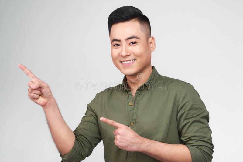 Lycklig upphetsad man som bort pekar på kopieringsutrymme med två fingrar som isoleras över vit bakgrund royaltyfri foto