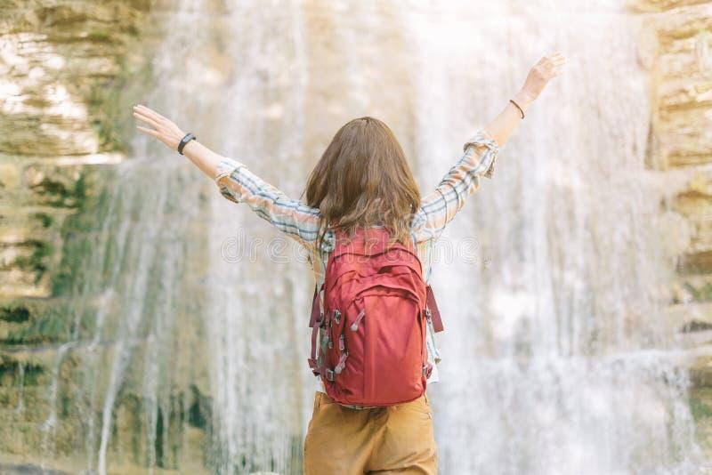 Lycklig utforskareflicka nära vattenfallet arkivfoton