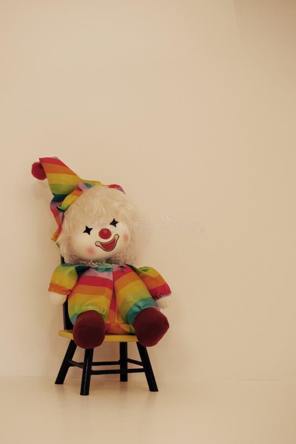 Lycklig vänd mot stol för regnbågeClownl Time Out royaltyfria foton