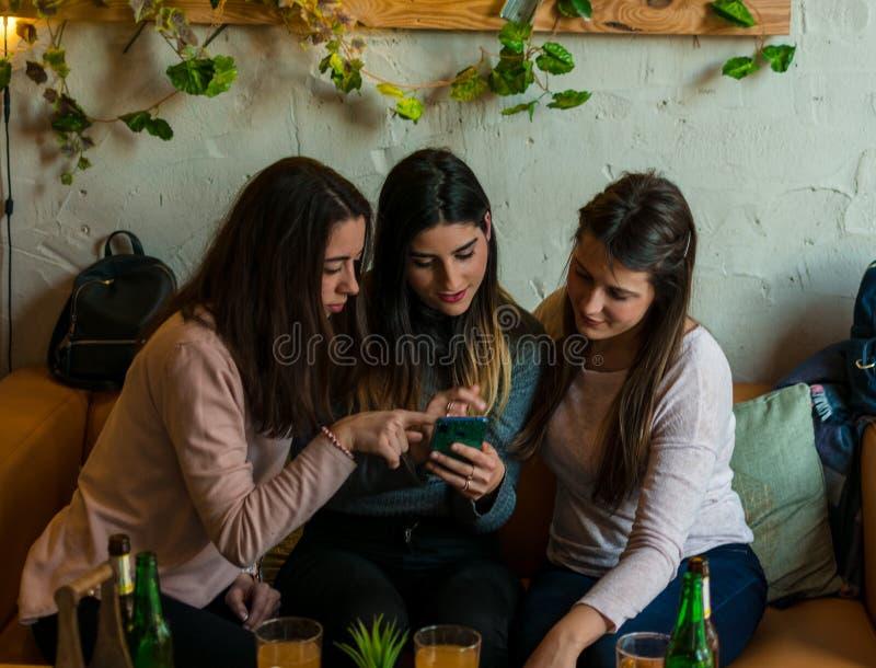 Lycklig vängrupp som dricker öl och ser en mobil på bryggeristångrestaurangen royaltyfria foton