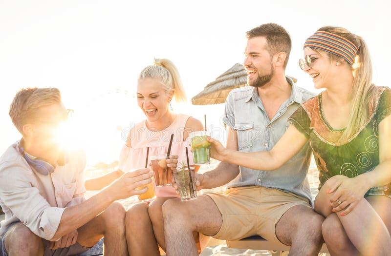 Lycklig vängrupp som har gyckel på strandpartiet som dricker coctailar royaltyfria foton