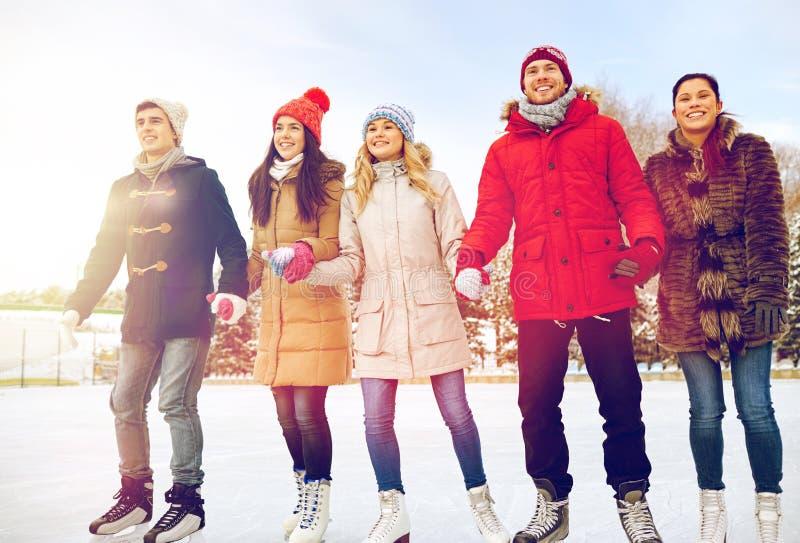 Lycklig vänskridskoåkning på isbana utomhus arkivfoto
