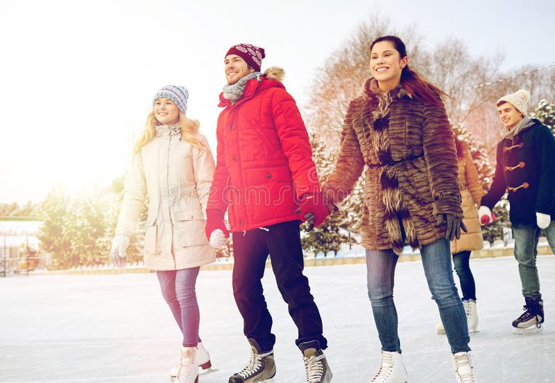 Lycklig vänskridskoåkning på isbana utomhus royaltyfri fotografi