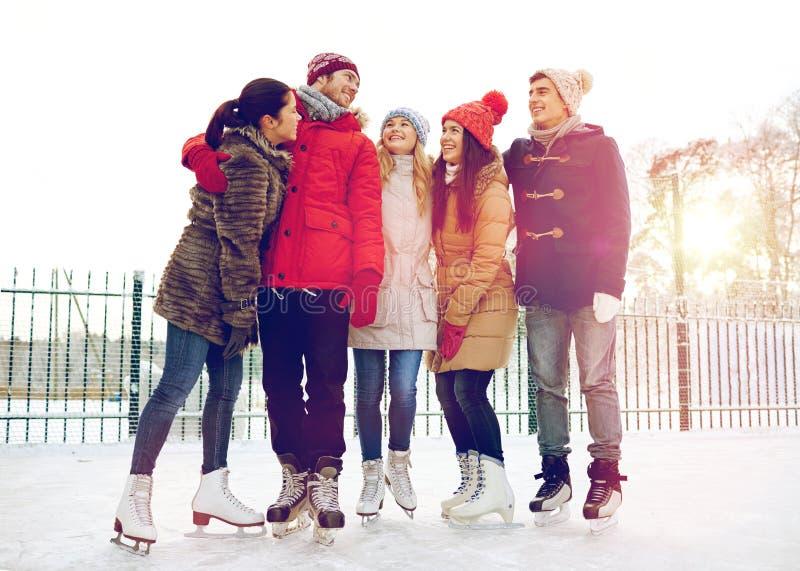 Lycklig vänskridskoåkning på isbana utomhus royaltyfri bild