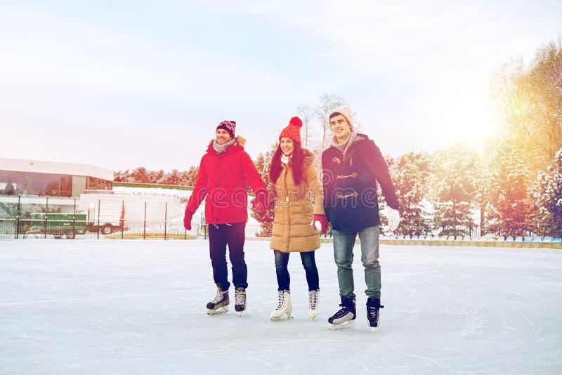 Lycklig vänskridskoåkning på isbana utomhus arkivbilder