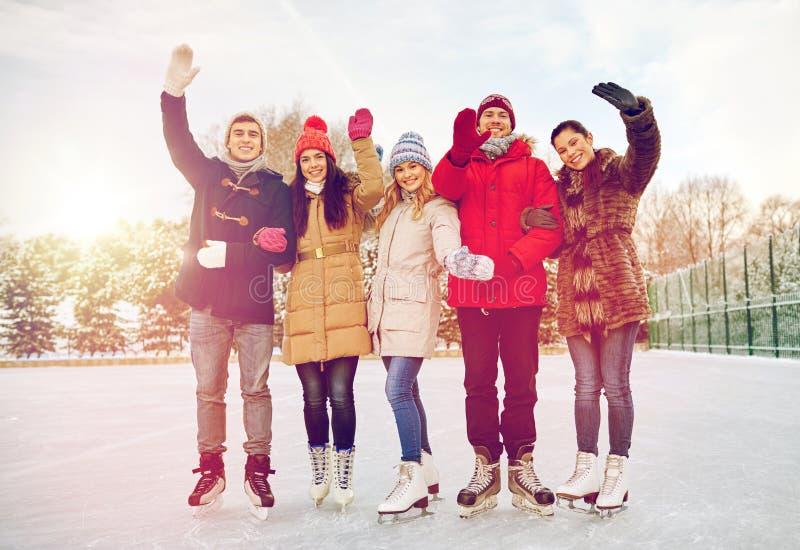 Lycklig vänskridskoåkning på isbana utomhus fotografering för bildbyråer