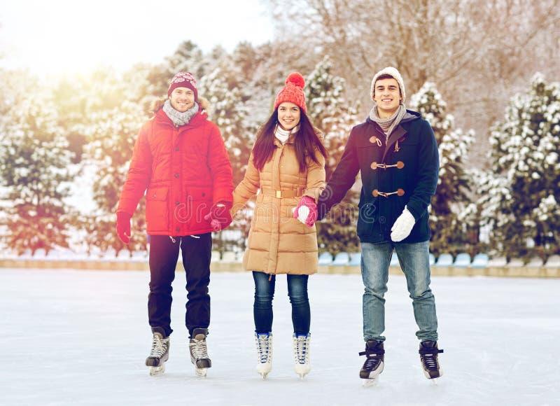 Lycklig vänskridskoåkning på isbana utomhus arkivfoton