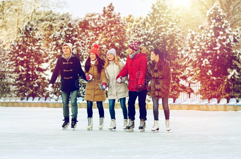 Lycklig vänskridskoåkning på isbana utomhus royaltyfria bilder