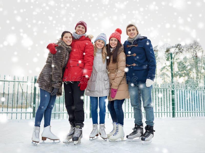 Lycklig vänskridskoåkning på isbana utomhus arkivbild