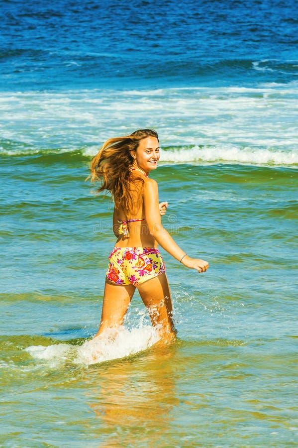 Lycklig vadande för ung kvinna på vatten arkivbild