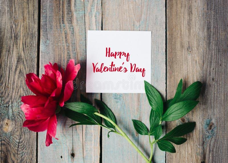Lycklig valentin dagtext på arket av papper, röd blomma på gammal lantlig träbakgrund fotografering för bildbyråer