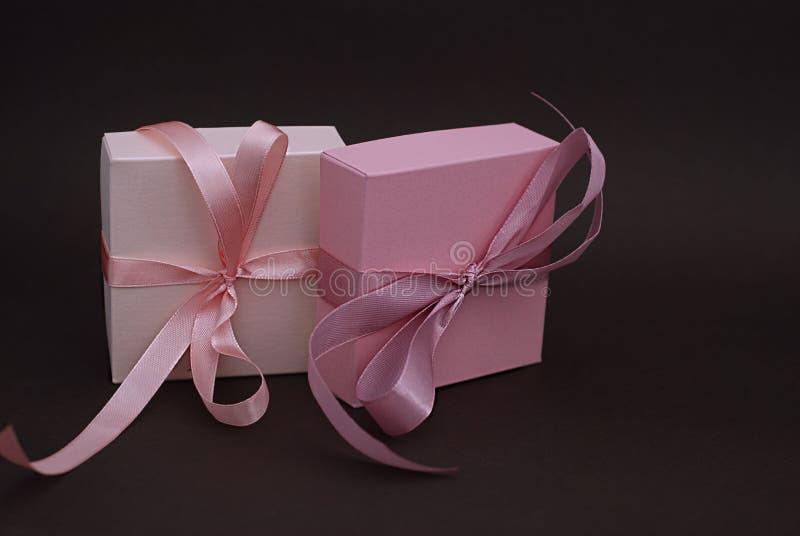 Lycklig valentine' s-dagbegrepp Rosa fyrkantigt pilbåge-band för gåvaask, mörk brun bakgrund arkivbilder