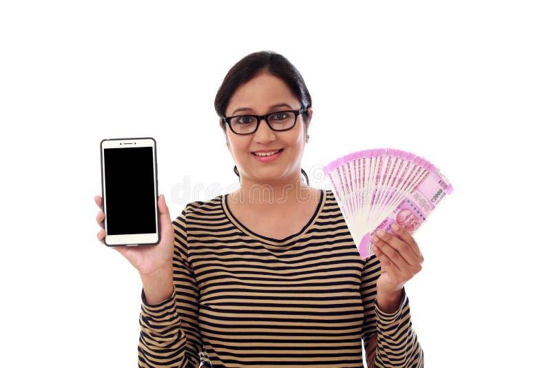 Lycklig valuta och mobiltelefon för ung kvinna hållande indisk royaltyfria bilder
