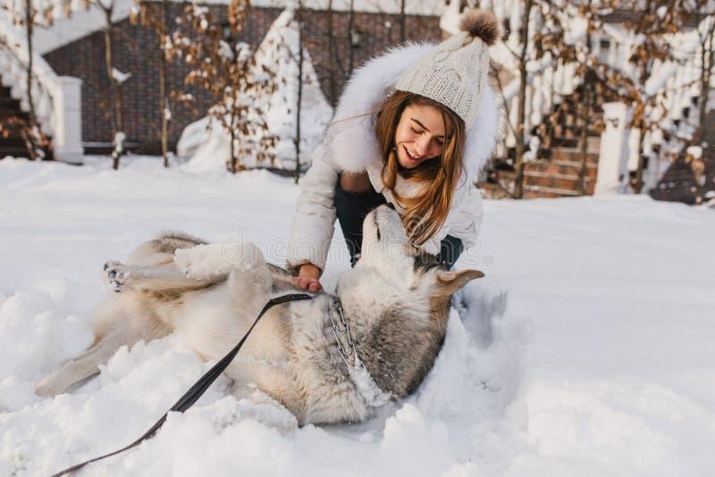 Lycklig vintertid av den glade unga kvinnan som spelar med den gulliga skrovliga hunden i sn? p? gatan Gladlynt lynne, positiva s arkivfoto