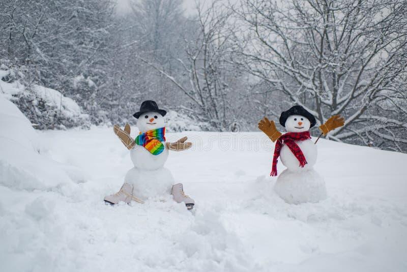 Lycklig vintertid Folk f?r julparti Lycklig le sn?gubbe tv? p? solig vinterdag Sinnliga snögubbepar royaltyfri bild