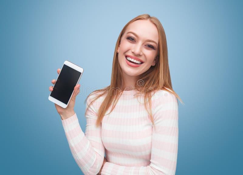 Lycklig visningsmartphone för ung kvinna i hand arkivfoto