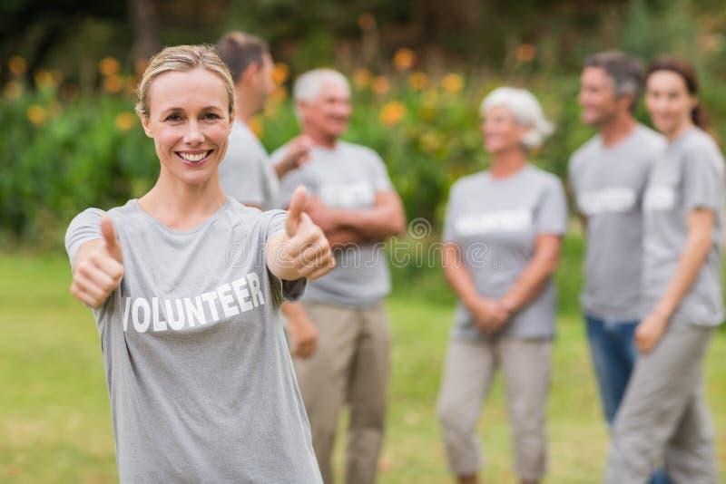 Lycklig volontär med tummen upp royaltyfri bild