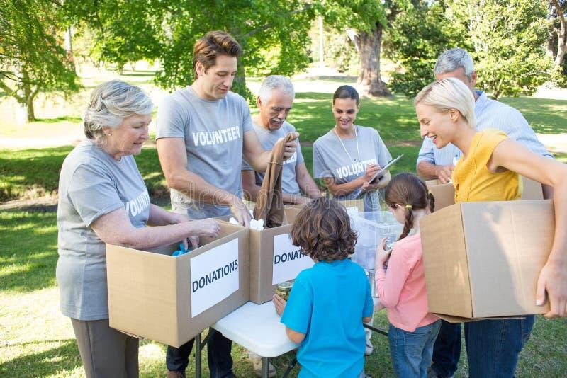 Lycklig volontärfamilj som avskiljer donationmaterial royaltyfri foto