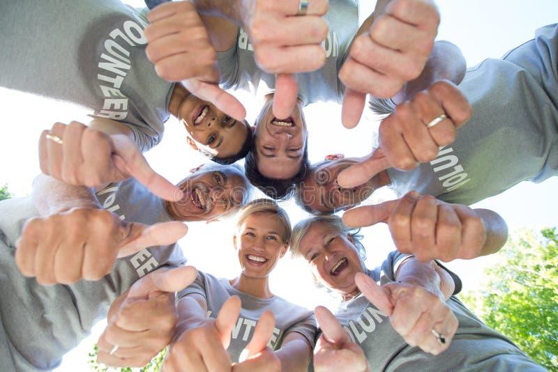 Lycklig volontärfamilj som ner ser med tummar upp arkivbild