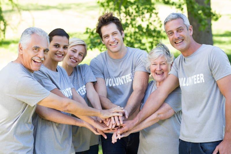 Lycklig volontärfamilj som tillsammans sätter deras händer arkivfoton
