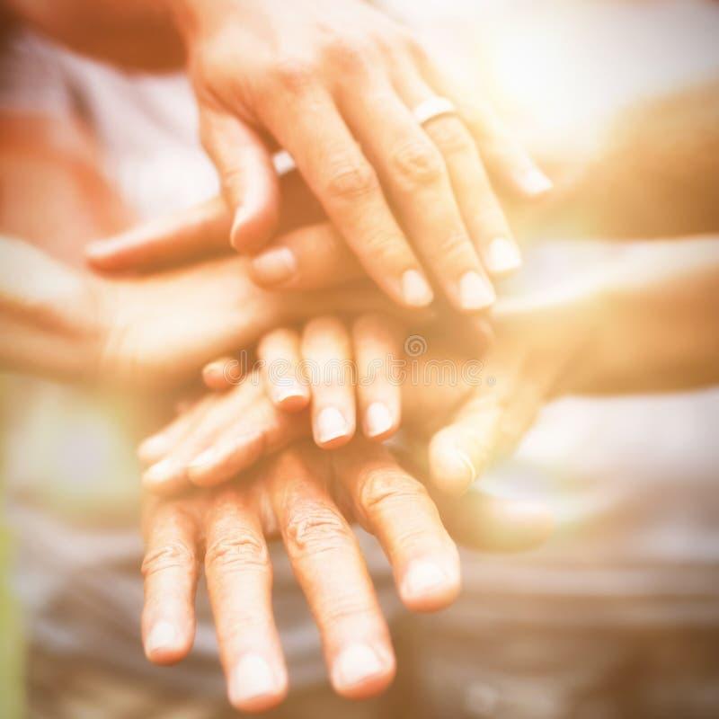 Lycklig volontärfamilj som tillsammans sätter deras händer arkivbild
