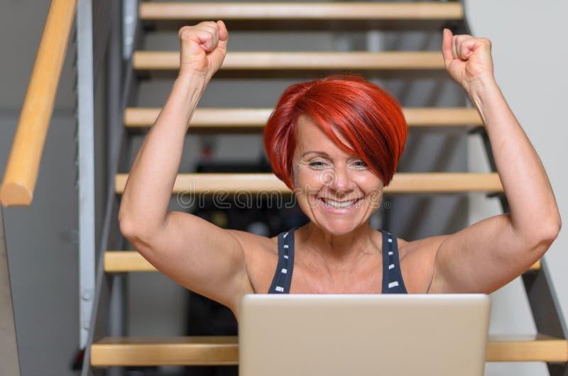 Lycklig vuxen kvinna med bärbara datorn som lyfter henne armar royaltyfri foto