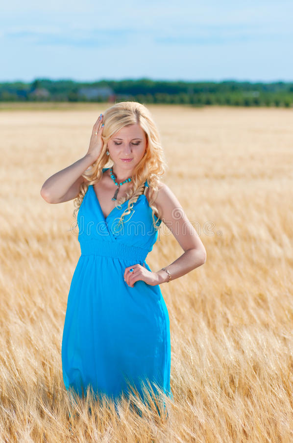 Lycklig womaninblåttklänning i guld- vete arkivfoto