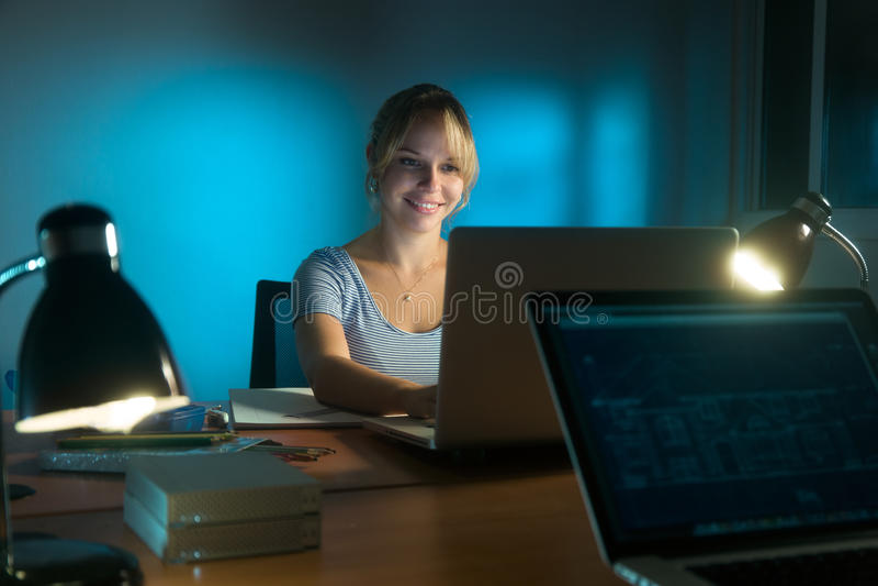 Lycklig Working On för kvinnainreformgivare PC sent på natten arkivfoto
