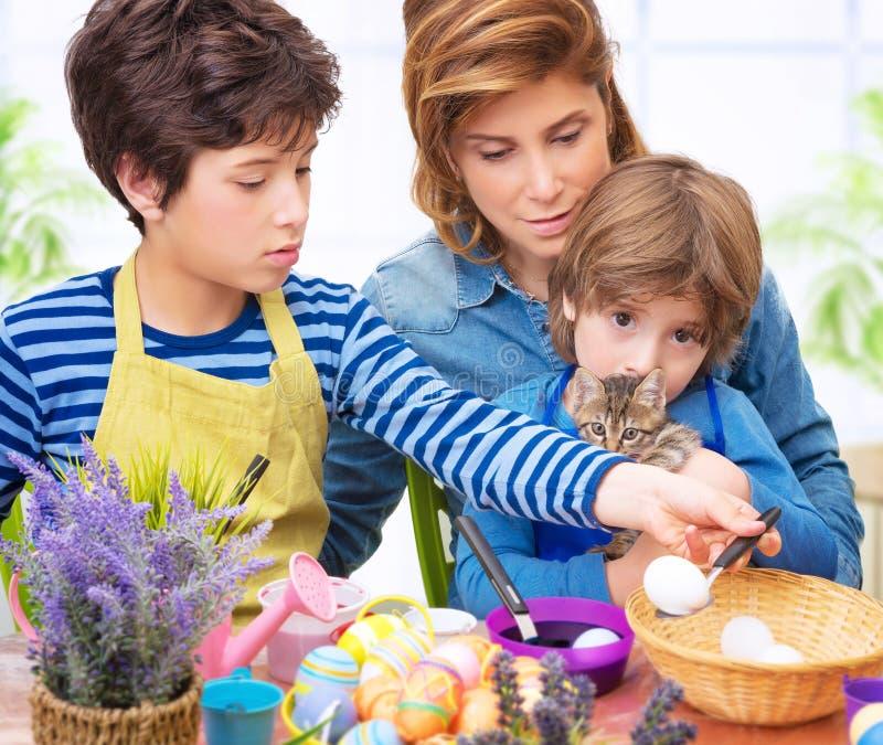 Lyckliga ägg för familjmålarfärgpåsk royaltyfri foto