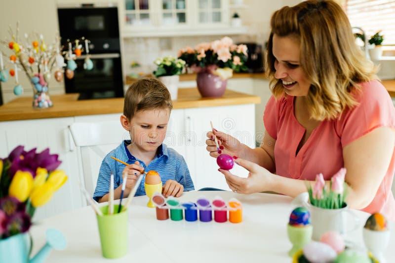 Lyckliga ägg för familjmålningpåsk arkivfoto