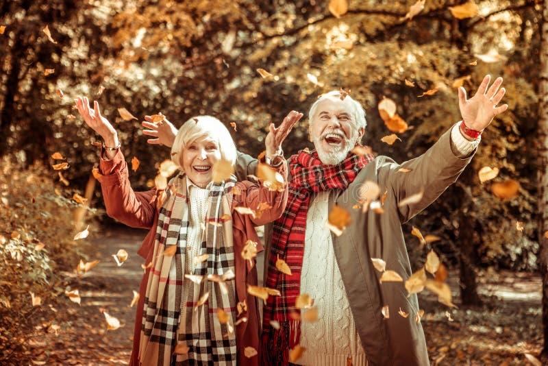 Lyckliga äldre par som kastar upp höstsidor royaltyfri foto