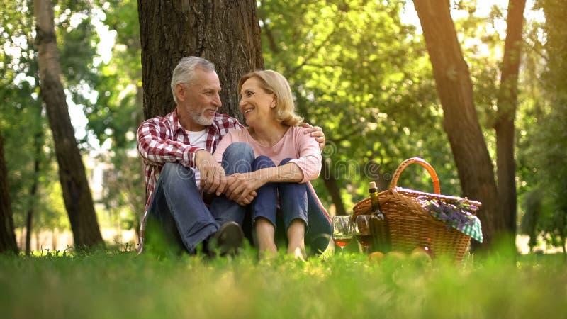 Lyckliga äldre par som sitter på gräs och tycker om det romantiska datumet, picknick parkerar in royaltyfri bild