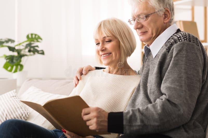 Lyckliga äldre par som tillsammans ser fotoalbumet fotografering för bildbyråer