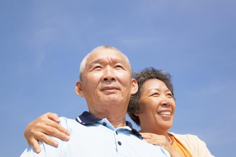 Lyckliga äldre pensionärpar med molnbakgrund royaltyfri foto