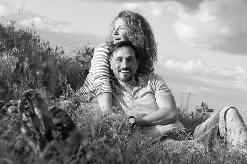 Lyckliga älska attraktiva par som lägger undan brasan som kramar i gräs och moln Utvändig stad för parförälskelsepicknick royaltyfri bild