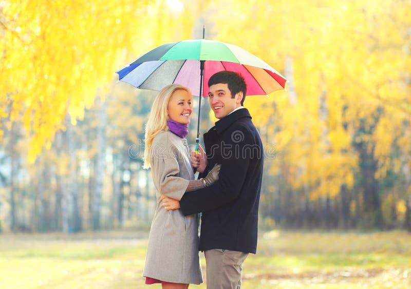 Lyckliga älska le par med det färgrika paraplyet i soligt parkerar royaltyfri bild