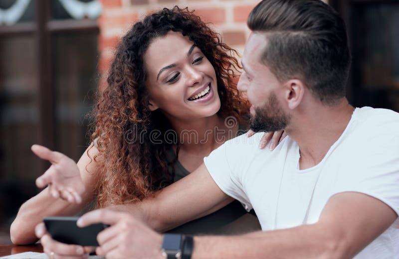 Lyckliga älska par genom att använda ett smartphonesammanträde i terrass royaltyfria foton