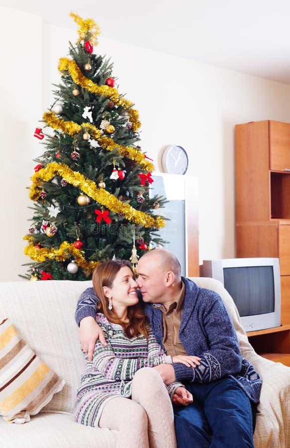 Lyckliga älska par near julgranen arkivfoto