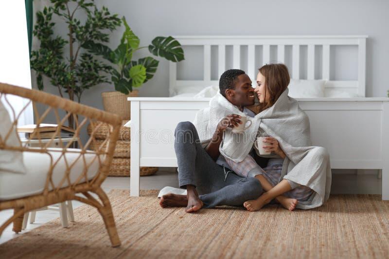 Lyckliga älska par som dricker kakao på vintermorgon i säng arkivbild