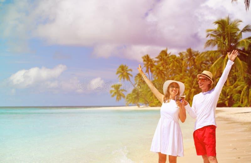 Lyckliga älska par som dricker vin på stranden royaltyfri bild