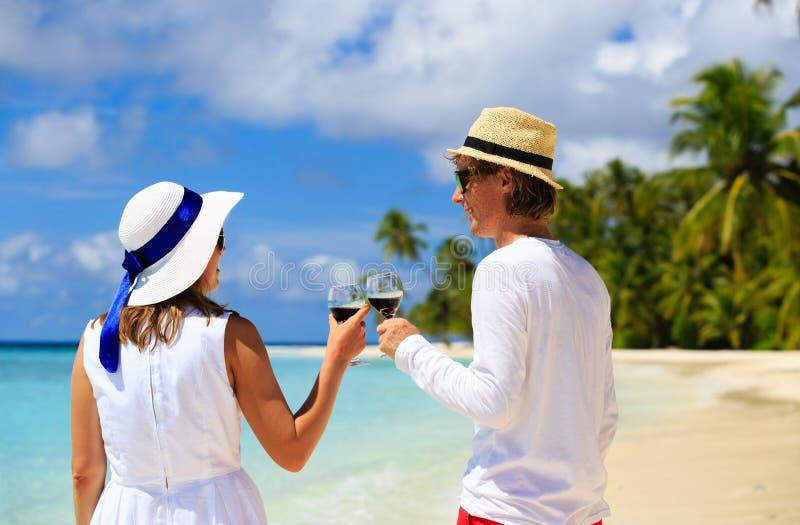 Lyckliga älska par som dricker vin på stranden arkivfoton