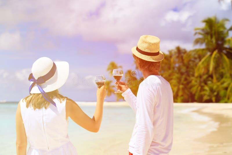 Lyckliga älska par som dricker vin på stranden arkivbild