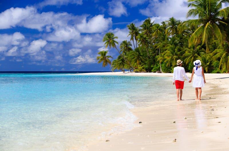 Lyckliga älska par som går på den tropiska stranden arkivfoton