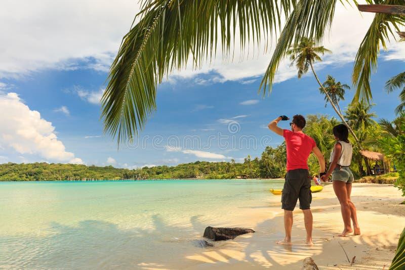 Lyckliga älska par som går på sommarstranden arkivfoton