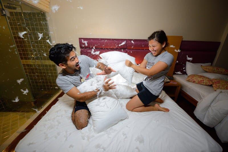 Lyckliga älska par som har en kuddekamp i säng på natten arkivfoto