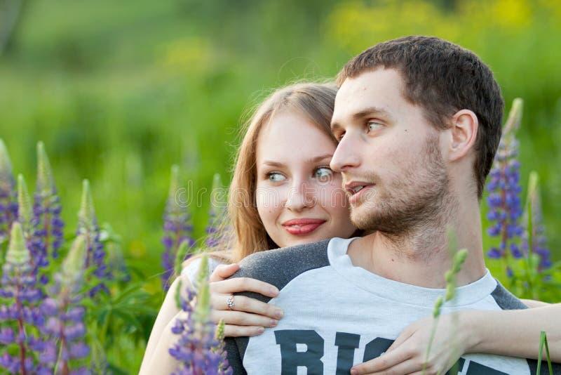 Lyckliga älska par som kramar i fält av lupine royaltyfri fotografi