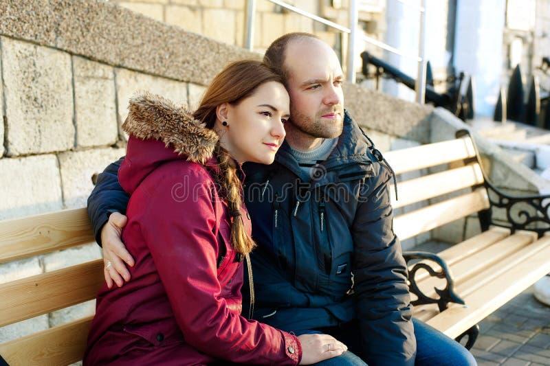 Lyckliga älska par som kramar i stad Stående av den unga attraktiva le mannen och kvinnan som kopplar av på en varm vinterdag på royaltyfri foto